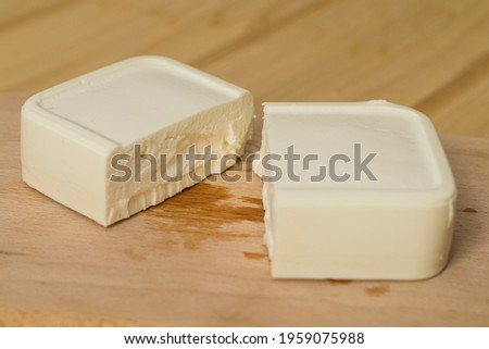 Feta cheese block broken in half on a wooden cutting board. Pieces of feta cheese close-up. Royalty-Free Stock Photo #1959075988