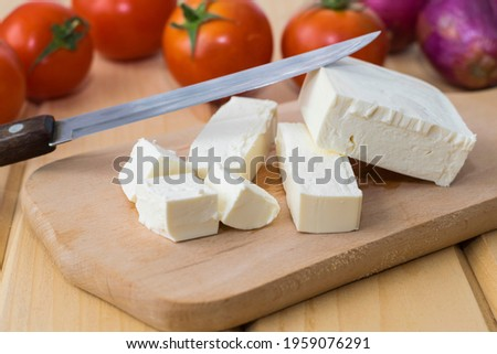 Sliced feta cheese on a wooden board on a background of tomatoes and onions. Royalty-Free Stock Photo #1959076291