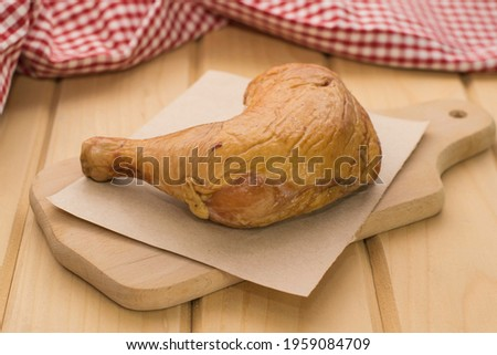 Smoked chicken quarter on a wooden cutting board. Royalty-Free Stock Photo #1959084709