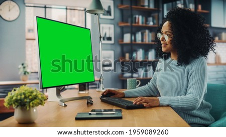 Latina Female Specialist Working on Desktop Computer with Green Screen Mock Up Display at Home Living Room while Sitting at a Table. Freelancer Female Chatting Over the Internet on Social Networks.