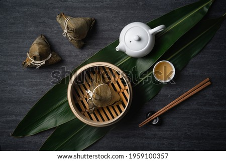 Zongzi Rice dumpling top view for Chinese traditional Dragon Boat Festival (Duanwu Festival) over dark black slate background.