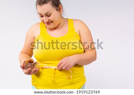 I am lazy to do something and addicted to sweets. A cheerful and full-mouthed woman, full of size, full of food, holding a plate of something tasty and eating, imitates her training