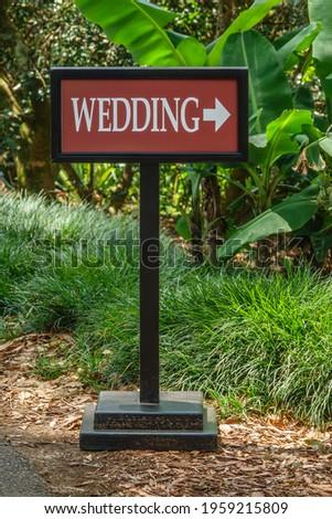 Directional portable wedding sign by a path in a public garden. Selective focus.