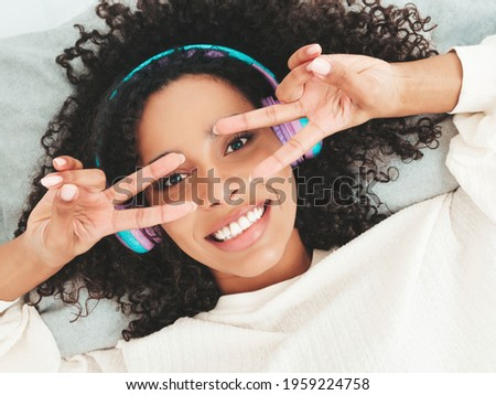 Beautiful black woman with afro curls hairstyle.Smiling model in sweater and jeans.Sexy carefree female listening music in wireless headphones in the morning.Lying in bed in white interior. Top view
