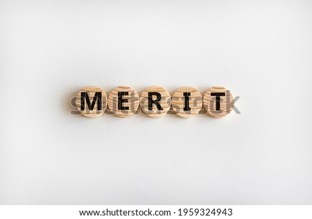 Merit symbol. Wooden circles with the word 'merit'. Beautiful white background, copy space. Business and merit concept.