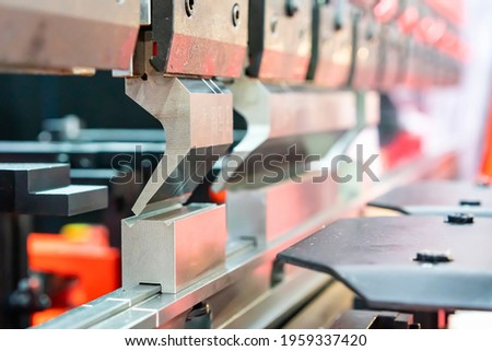 Close up upper move bending blade or punch and fix die of automatic and high precision cnc hydraulic press bending machine for metal sheet forming in industrial Royalty-Free Stock Photo #1959337420