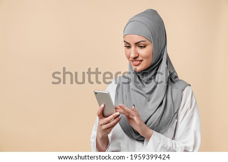 Smiling smart young islamic middle eastern arabian muslim woman using smart phone isolated over beige background. Young female in grey hijab typing messages on cellphone, chatting, surfing Internet Royalty-Free Stock Photo #1959399424