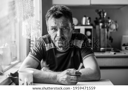 Portrait of male worker in his rural home. Black and white photo.