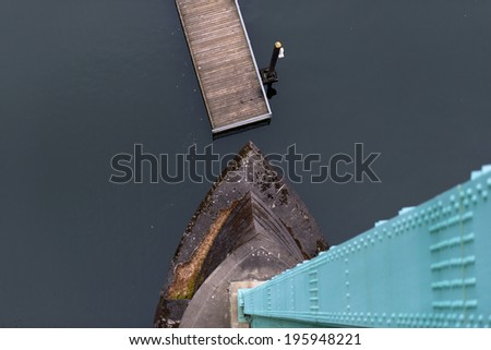 Modern Top view of the green support and concrete foundation of the bridge, the dark water and the wooden pier with a restrictive column. Avant-garde #195948221