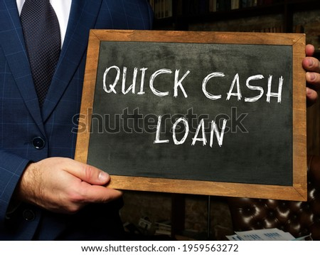 Business concept about QUICK CASH LOAN with sign on chalkboard in hand.