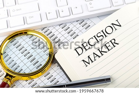 DECISION MAKER text on the notebook with chart, magnifier,keyboard and pen