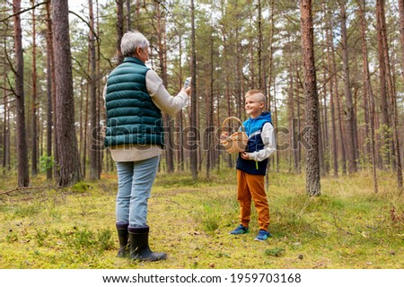 picking season, leisure and people concept - grandmother with smartphone photographing happy smiling grandson with mushrooms in basket in forest