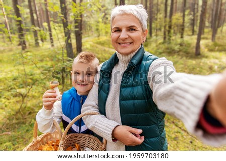 picking season, leisure and people concept - grandmother and grandson with baskets and mushrooms taking selfie in forest