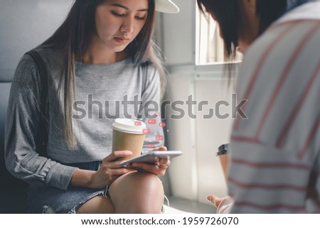 Young Asian woman passenger using a social media marketing concept on mobile phone with notification icons of like, message, comment and star above smartphone screen inside empty subway or  train.