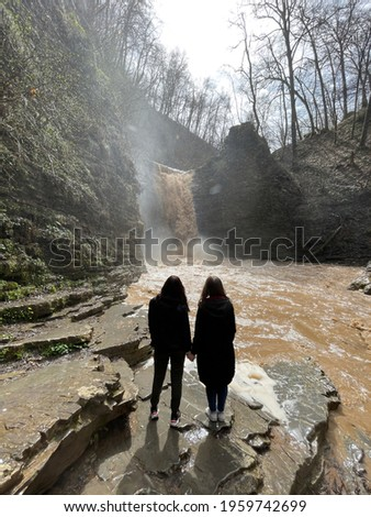 Rear view of two women looking on powerful muddy waterfall. Tourists standing on rocks in mountainous terrain and enjoying beautiful view of cataract Royalty-Free Stock Photo #1959742699