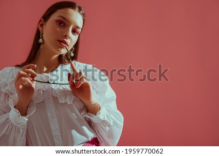 Fashionable elegant girl wearing trendy white vintage cotton blouse with lace collar, stylish pearl earrings, holding glasses, posing on pink background. Copy, empty space for text