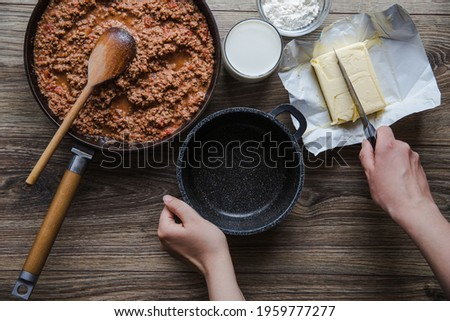 Woman cooking homemade classic lasagna bolognese, on dark table; with ingredients, top view copy space, hands in picture