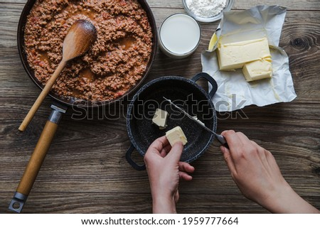 Woman cooking homemade classic lasagna bolognese, on dark table; with ingredients, top view copy space, hands in picture.