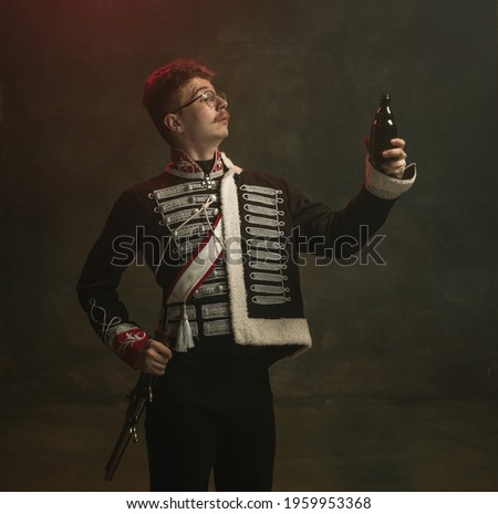 Beer time. Young man in suit as royal person isolated on dark green background. Retro style, comparison of eras concept. Beautiful male model like historical character, monarch, old-fashioned. Royalty-Free Stock Photo #1959953368