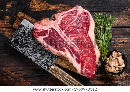 Italian Florentine T-bone beef meat Steak with herbs on a wooden cutting board. Dark wooden background. Top view Royalty-Free Stock Photo #1959979312