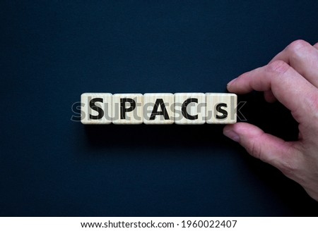 SPACs symbol. Wooden cubes with words 'SPACs, special purpose acquisition companies' on beautiful black background, copy space. Businessman hand. Business and SPACs concept.