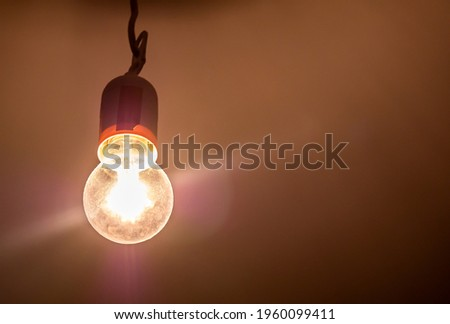 One single old plain bright incandescent lightbulb on in a darkened room, object detail, closeup, from below Bright yellow light source illuminates the room, light in the dark abstract concept, nobody Royalty-Free Stock Photo #1960099411