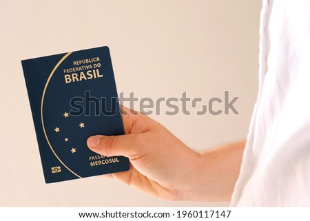 Person holding Brazilian Passport. Travel concept. | Translation: Federative Republic of Brazil. Mercosur passport. Royalty-Free Stock Photo #1960117147
