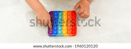 Anonymous child with colorful poppit game. Close up bunner shot of kid hands playing with colorful pop It fidget toy. Royalty-Free Stock Photo #1960120120