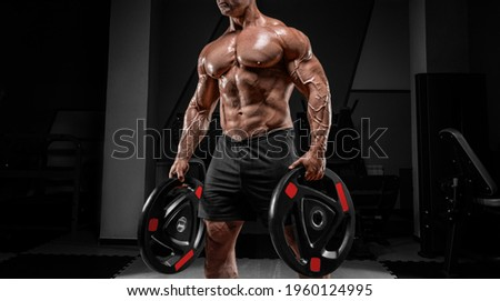 Muscular man stands in a gym with barbell discs. Bodybuilding and powerlifting concept. Mixed media Royalty-Free Stock Photo #1960124995
