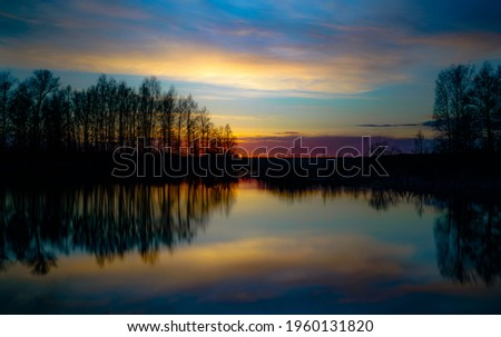sunset at coast of the lake. Nature landscape. Nature in northern Europe. reflection, blue sky and yellow sunlight. landscape during sunset. Royalty-Free Stock Photo #1960131820