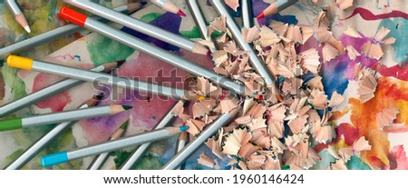 Set wooden color pencils. Wooden pencil shavings and colorful crumbs of graphite from sharpener on abstract background. Crayons close up, back to school wallpaper. Art time image