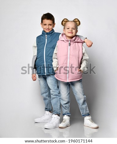 Studio shot of little brother with sister in warm outerwear blue and pink vests, jeans, sneakers and sweatshirt posing for the camera, isolated on white. Advertising of children's fashion clothes Royalty-Free Stock Photo #1960171144