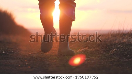 A farmer in rubber boots and a tablet in his hands walks through the green field in rubber boots, the concept of farming business, view the planted shoots of crops, the harvest of eco-crops