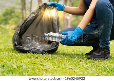 environment protection pollution problems and global warming,plastic waste caring about nature concept.Volunteer women carrying garbage bags, garbage collection, cleaning in the national park Royalty-Free Stock Photo #1960245922