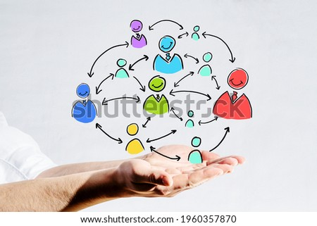Hand holding a scheme of colorful people signs and arrows between them on a white background, communication and connection concept