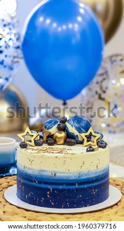 Handmade birthday cake on a blurred background with balloons and sparkles. Cheesecake cake, blue and gold accents. Festive background for postcard, holiday, birthday, anniversary, 18 years.  Royalty-Free Stock Photo #1960379716