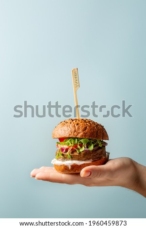 Hand holding burger. Hamburger with meat free plant based cutlet, tomatoes, onions, white sauce and microgreens on blue background. Healthy vegan or vegetarian food concept. Copy space. Royalty-Free Stock Photo #1960459873