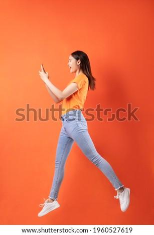 Young Asian woman wearing orange T-shirt jumping on orange background