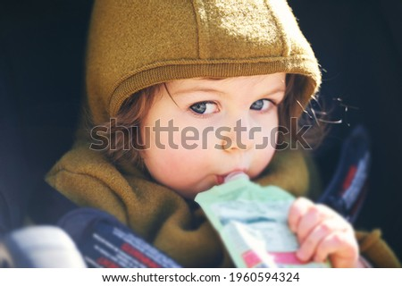 Close up portrait of sweet toddler kid eating fruit puree from plastic doy pack, sitting in stroller, outdoor snack time Royalty-Free Stock Photo #1960594324