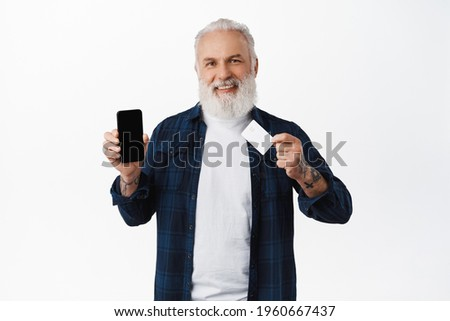 Happy stylish old man showing mobile phone screen and credit card, smiling pleased, recommending application on smartphone for payment, paying online, standing over white background