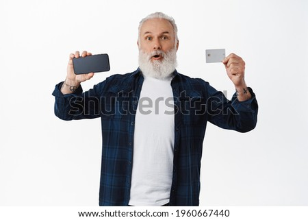 Surprised senior man showing smartphone screen and credit card, gasping and say wow. Excited mature man recommending online shopping app, contactless payment, white background
