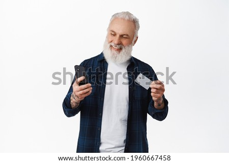 Handsome mature man paying with credit card on smartphone, showing card and looking at phone with smiling face, shopping online, standing against white background
