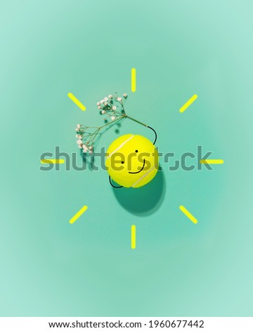 Spring sport composition with large tennis ball in the form of a smiley face and flower on blue background. The concept of good mood and well-being from sports activities. Minimalistic design