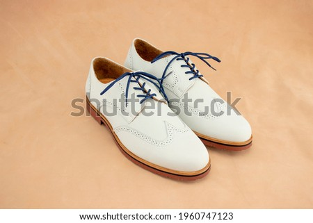 A pair of white nubuck bucks with a bright blue laces on. This fashionable footwear is a classic for mens leather shoes. Royalty-Free Stock Photo #1960747123