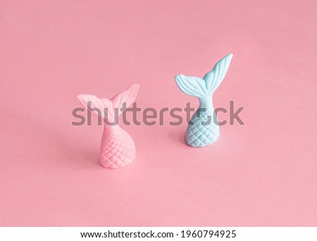 Mermaids tails, pink and blue against pastel pink background. Creative composition, under the sea theme.