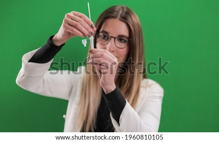 Corona Antigen Self-Test in use - young woman applies a Covid-19 self-test - studio photography