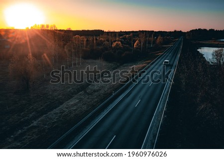 Long country road with white lines down the centre stretching off past a lone tree to the distant horizon Royalty-Free Stock Photo #1960976026
