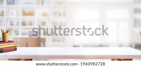 Cropped shot of white table with books, stationery and copy space in blurred study room Royalty-Free Stock Photo #1960982728