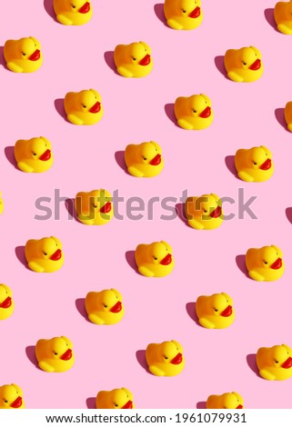 Trendy sunlight isometric view child yellow rubber duck toy vertical background. Seamless still life seamless pattern on a pastel pink background. Minimal creative summer or kid concept.