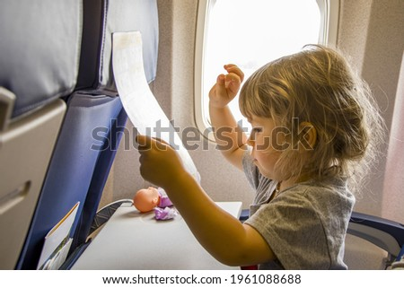 Portrait of a little girl in the cabin of the plane near the window, looking at the pictures of the magazine.